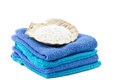 Aqua and blue towels with scallop shell on top filled bath salt Royalty Free Stock Photography