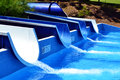 Aqua park slides with running water to a swimming pool Royalty Free Stock Photos