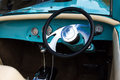 Aqua vintage car interior steering wheel of coloured sports showing gear shift and meters Stock Images