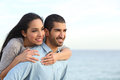 Arab couple flirting in love on the beach piggyback with sea background Stock Photo