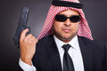 Arab hit man holding gun on black background Stock Photos