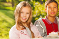 Arabian boy and blond girl sitting at wooden table outside with cupcake during sunny autumn day Royalty Free Stock Photos
