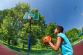 Arabian boy ready to throw ball in basketball goal on the playground outside during sunny summer day Royalty Free Stock Photos
