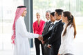 Arabian businessman employees handshaking with group of his in office Royalty Free Stock Images