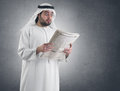 Arabian businessman shocked reading newspaper Stock Photography