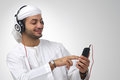 Arabian guy listening to music using headphones isolated Royalty Free Stock Image