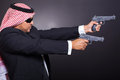Arabian hit man dangerous shooting with two guns over black background Royalty Free Stock Image