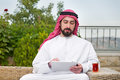 Arabian man working on a mobile tablet & drinking tea Royalty Free Stock Photography