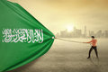 Arabian person dragging flag of Saudi Arabia Royalty Free Stock Photo