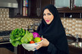 Arabian woman wearing holding a bowl of veggies in the kitchen Stock Photo