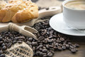 Arabica coffee beans with a cup of coffee black and pastry on brown wood board Stock Photography