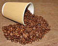 Arabica coffee beans and takeaway cup spilling out of a disposable paper with a wood texture background Royalty Free Stock Photography