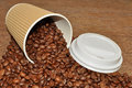 Arabica coffee beans and takeaway cup spilling out of a disposable paper with a wood texture background Royalty Free Stock Photo