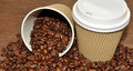 Arabica coffee beans and takeaway cup spilling out of a disposable paper with a wood texture background Stock Image
