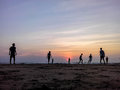 Boys playing football on the beach, beautiful sunset in background