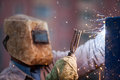 Arc welder worker in protective mask welding metal construction heavy industry hand holding torch working on Stock Photo
