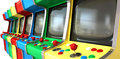 Arcade game machines row a flat of vintage unbranded games with joysticks and various colored buttons and a blank screen on an Royalty Free Stock Images