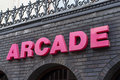 Arcade sign pink lettering brick wall background Stock Photos