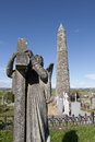 Archangel gravestone before an ancient round tower angel statue and celtic graveyard with cathedral in ardmore county waterford Royalty Free Stock Photos