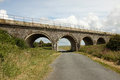 Arched bridge a single track road leads to an stone with a height restriction sign and warning strip Stock Photo