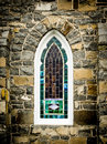 Arched Stained Glass Window in Stone Wall Royalty Free Stock Photo