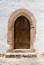 Arched door ancient wooden with stone archway and stucco white wall Stock Image