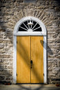 Arched door in old stone wall an doorway set an vintage architectural detail of stonework the victorian high gothic style Royalty Free Stock Photo