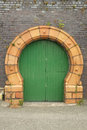 Arched doorway a green painted wooden door with a yellow arch designed with cast brick against an old blue brick wall with plants Royalty Free Stock Images