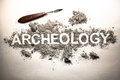 Archeology word written in letters on a pile of ash, dirt, soil, ground as excavation of history artifact concept background. Sea Royalty Free Stock Photo