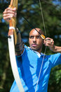 Archer aiming at target with bow and arrow bowman or Stock Photos