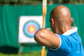 Archer aiming at target with bow and arrow bowman or Stock Images