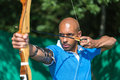 Archer aiming at target with bow and arrow bowman or Royalty Free Stock Images