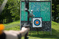 Archer holds his bow aiming at a target selective focus Stock Images