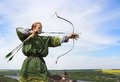 Archer young with bow and arrows in medieval costume aiming Stock Image