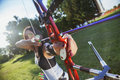 Archery attractive female practicing at the range focus is on bow Royalty Free Stock Photos
