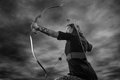 Archery woman beautiful aiming sky on background black and white image Stock Image