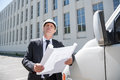 Architect with blueprint standing near car and looking up Royalty Free Stock Photo