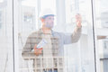Architect with blueprints photographing through mobile phone in office Royalty Free Stock Photo