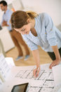 Architect checking blueprint young woman working in office Royalty Free Stock Photo
