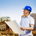 Architect on construction site holding blueprint at the Stock Photos