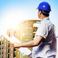 Architect on construction site holding blueprint and observe the Royalty Free Stock Images