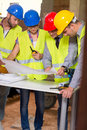 Architect explaining building plan to colleagues male at construction site Royalty Free Stock Image