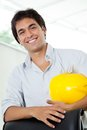 Architect holding hardhat portrait of happy young male yellow while standing by office chair Royalty Free Stock Images