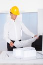 Architect looking at blueprint male analyzing with architectural model on desk Royalty Free Stock Photography