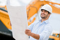 Architect looking at blueprints in a building site Royalty Free Stock Photo