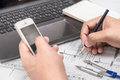 Architect reviewing a blueprint by adjusting the measurement wit with pen smart telephone and laptop Royalty Free Stock Image