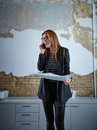 Architect woman talking phone holding plan paper Royalty Free Stock Photo