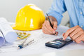 Architect working at desk close up of male drawing on blueprint and using calculator Stock Photography