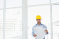 Architect in yellow hard hat looking at blueprint in office serious young a bright Royalty Free Stock Image