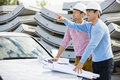 Architects with blueprints on car discussing at site Royalty Free Stock Photo
